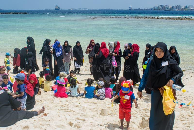Moslemische Frauen und Kinder, die Feiertage am tropischen Strand verbringen stockfoto