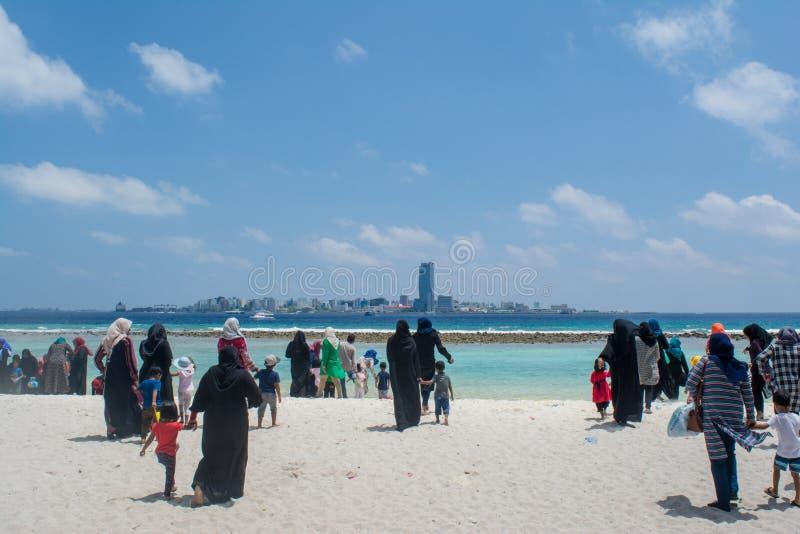 Moslemische Frauen und Kinder, die in Richtung zum Ozean am tropischen Strand gehen lizenzfreies stockbild