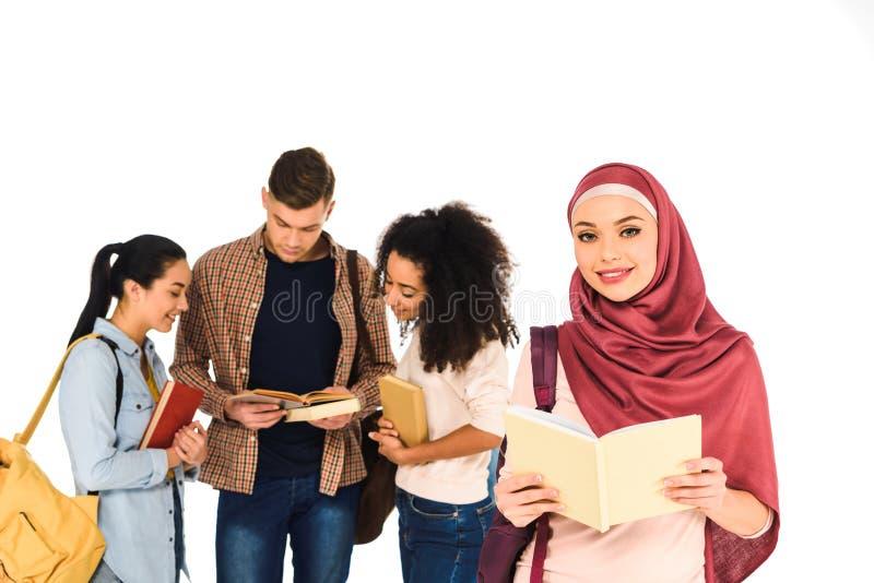 moslemische Frauenstellung mit Buch nahe multiethnischer Gruppe jungen Leuten lokalisiert stockfoto
