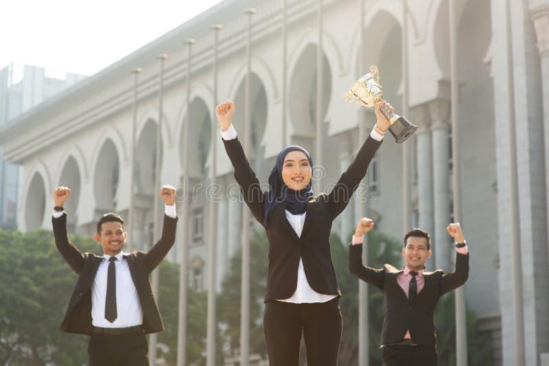 Moslemische Geschäftsfrau, die eine Trophäe hält stockfoto