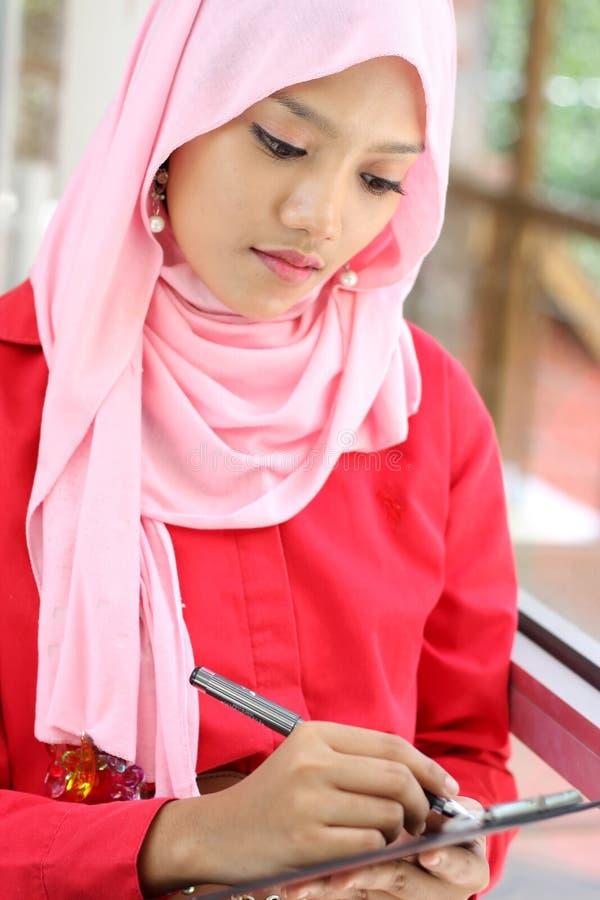 Moslemische Geschäftsfrau mit einer Listendatei stockfotos
