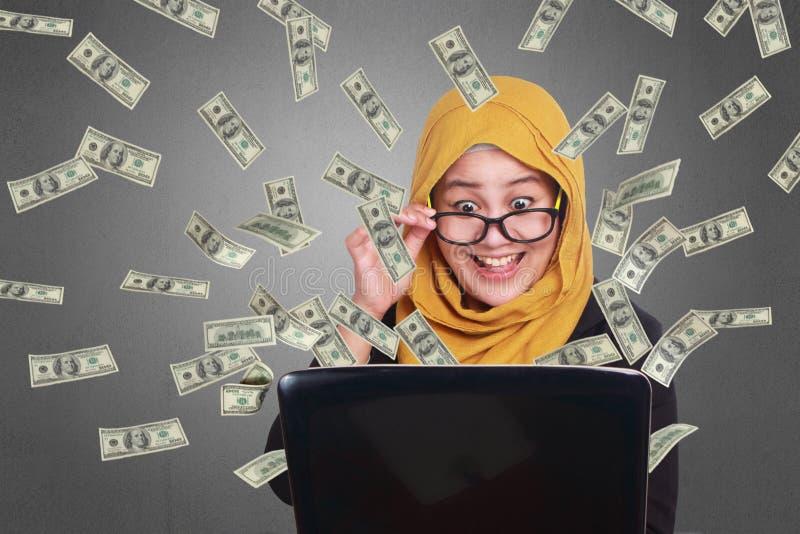Moslemische Geschäftsfrau Working auf Laptop mit Regen des Geldes lizenzfreies stockfoto