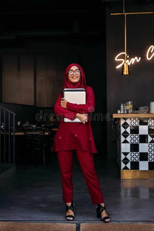 Moslemische Geschäftsfraustellung an der Restauranttür lizenzfreie stockfotos