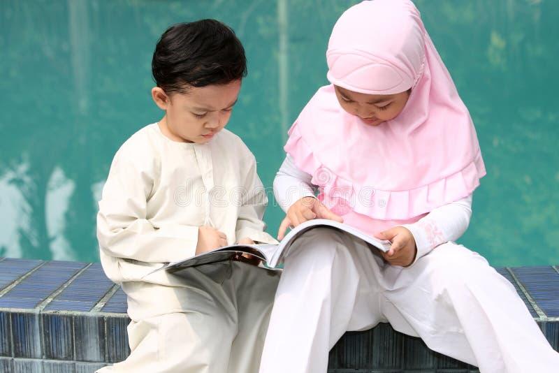 Moslemische Kinder, die ein Buch lesen lizenzfreies stockbild