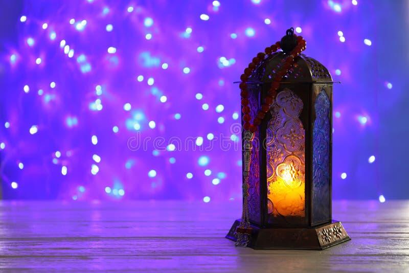 Moslemische Lampe mit Kerze auf Tabelle verwischte feenhafte Lichter Fanous als Ramadan-Symbol lizenzfreie stockfotografie