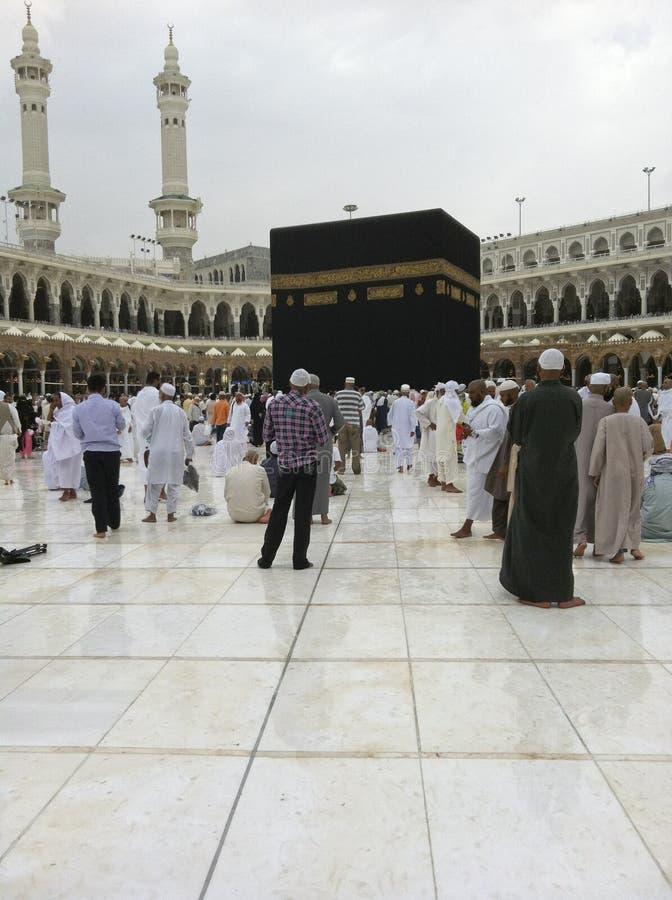 Moslemische Pilgerer gehen ein nach hellem Nieselregen stockfotos
