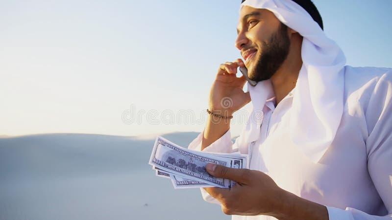 Moslemischer männlicher Geschäftsmann spricht am Telefon und teilt Nachrichten mit Baut. stockbild