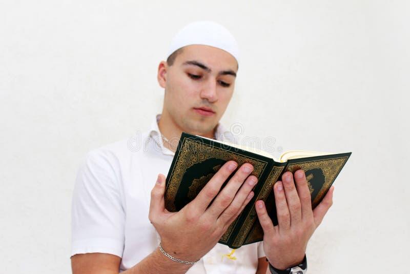 Moslemischer Mann, der den Koran liest stockbilder