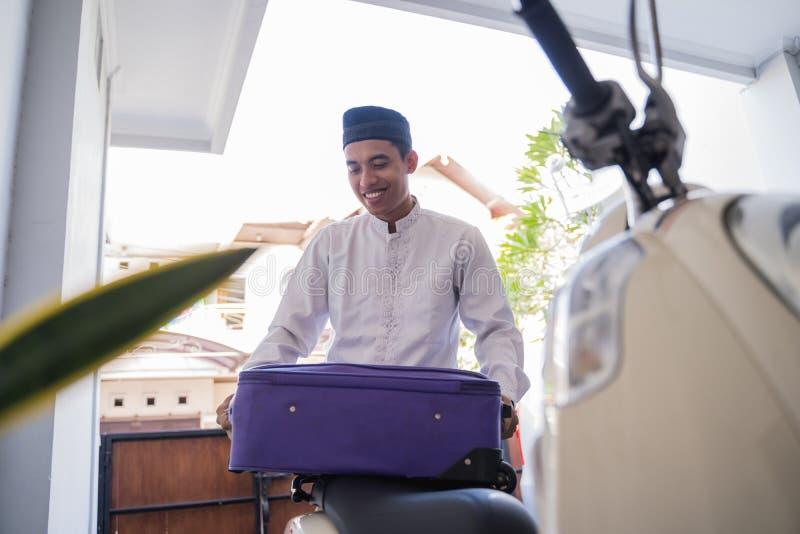 Moslemischer Mann, der für eid Mubarak-lebaran durch motorcyle reist lizenzfreies stockbild
