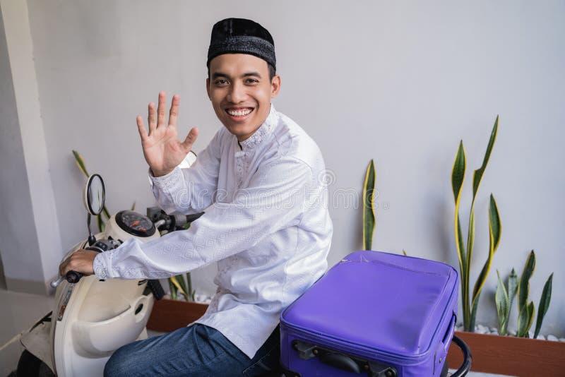 Moslemischer Mann, der für eid Mubarak-lebaran durch motorcyle reist lizenzfreies stockfoto