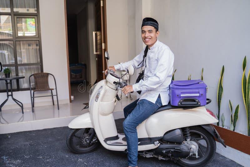 Moslemischer Mann, der für eid Mubarak-lebaran durch motorcyle reist stockfotografie