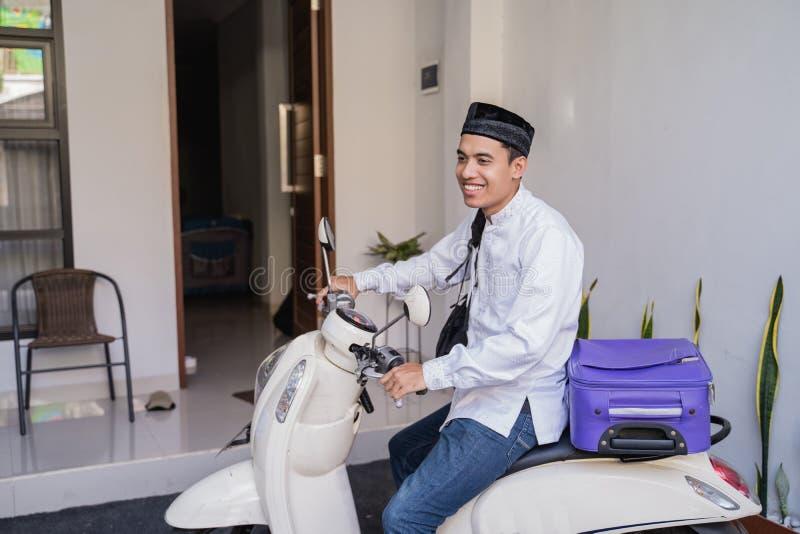 Moslemischer Mann, der für eid Mubarak-lebaran durch motorcyle reist stockfoto