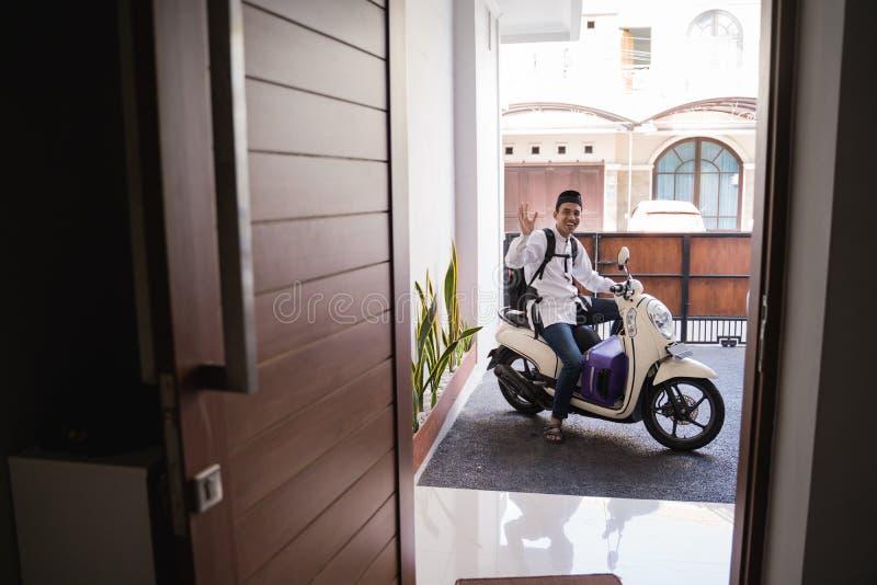 Moslemischer Mann, der für eid Mubarak-lebaran durch motorcyle reist stockbilder