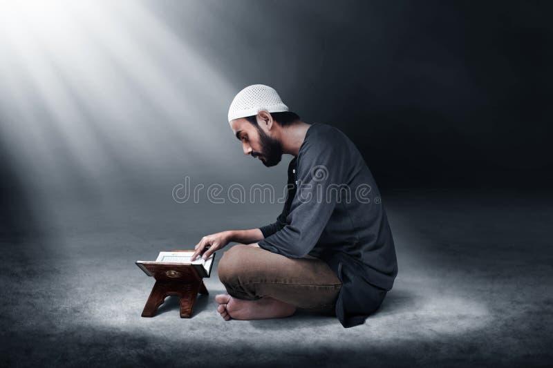 Moslemischer Mann, der heiligen Quran liest lizenzfreie stockfotografie