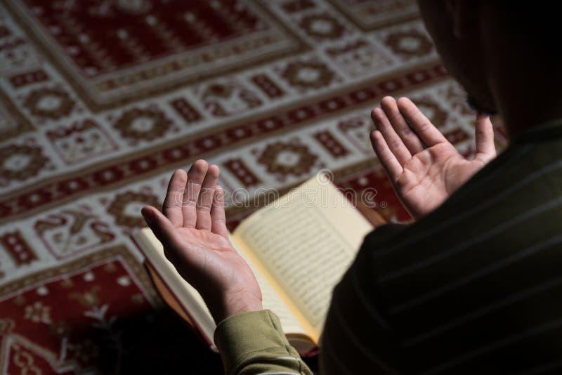 Moslemischer Mann liest den Koran lizenzfreie stockbilder
