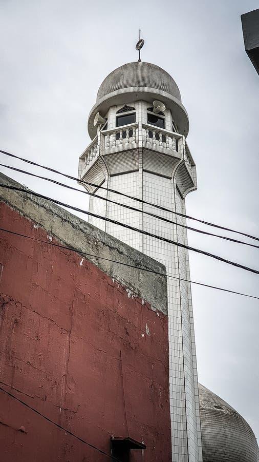 Moslemischer Moscheen-Turm gegen Stadtgebäude und elektrische Leitungen lizenzfreie stockbilder