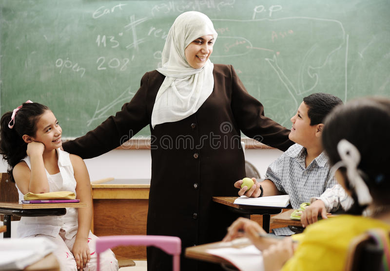 Moslemischer weiblicher Lehrer mit Kindern im Klassenzimmer lizenzfreies stockbild