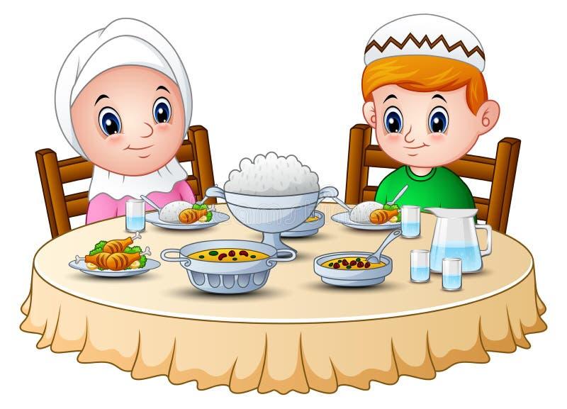 Moslemisches Kind beten zusammen, bevor er Bruchfastet stockbild
