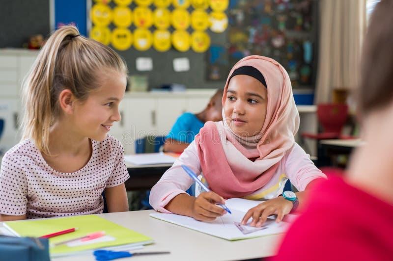 Moslemisches Mädchen mit ihrem Mitschüler stockfotos