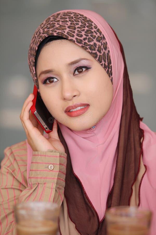 Moslemisches Mädchengebrauch-Mobiltelefon lizenzfreie stockfotos