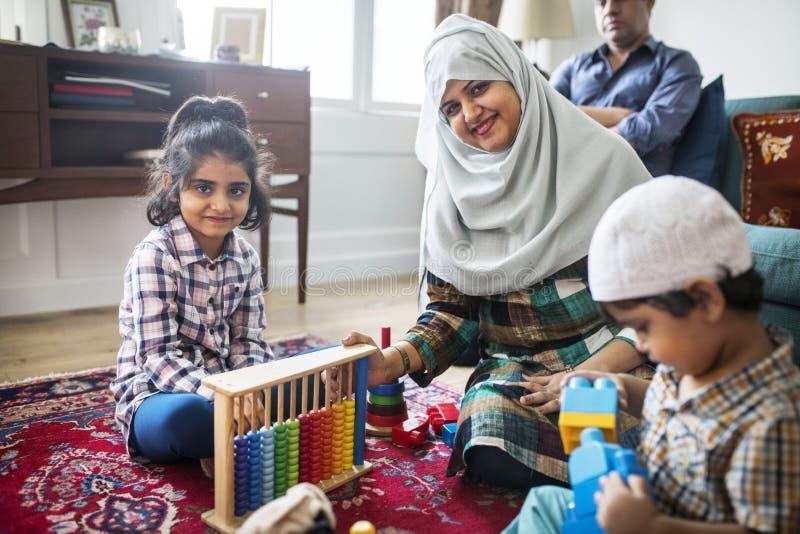 Moslim en familie die thuis ontspannen spelen stock foto's