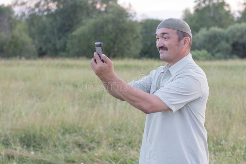 Moslim hogere mens die beelden op een mobiele telefoon nemen royalty-vrije stock foto's