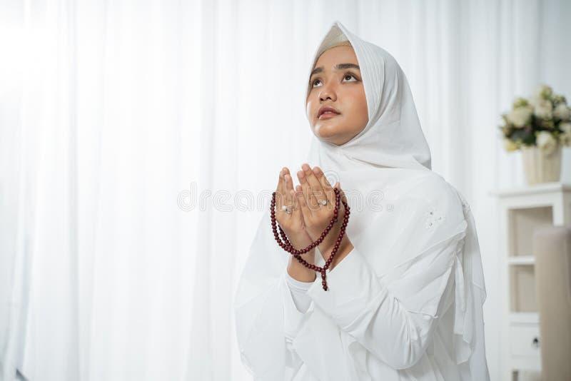 Moslim jonge vrouw die in witte traditionele kleren bidden royalty-vrije stock fotografie
