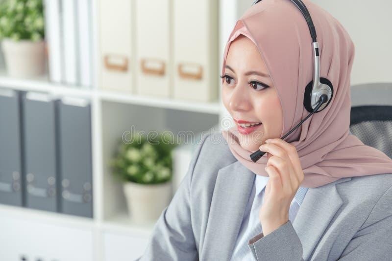 Moslim vrouwelijke dienst met tussenkomst van de telefonistklanten stock afbeeldingen