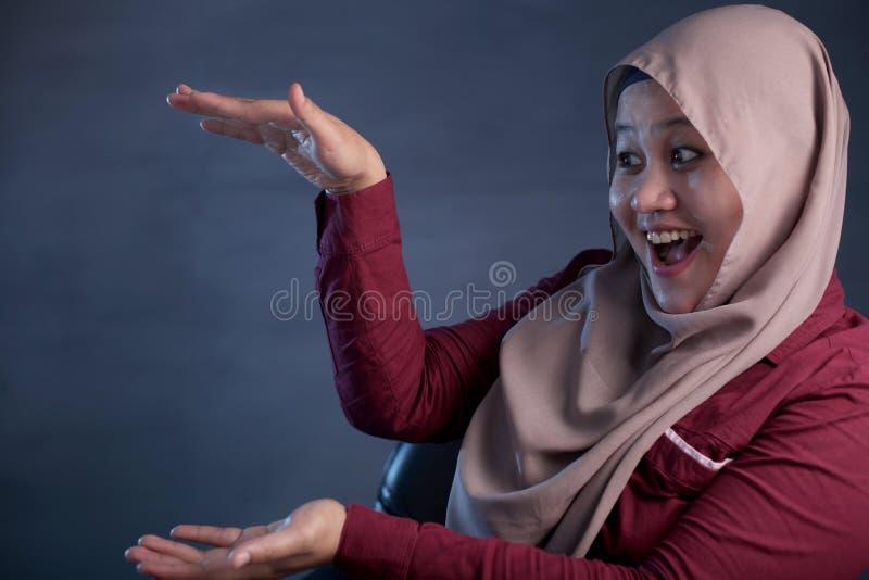 Moslimdame Presenting Something aan Haar Kant met Exemplaarruimte stock afbeeldingen