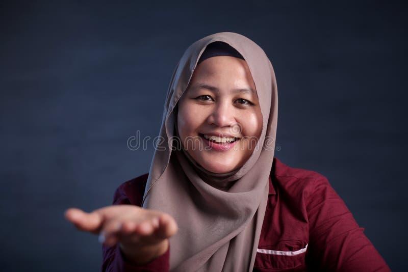 Moslimdame Shows Something in Haar Lege Hand royalty-vrije stock afbeeldingen