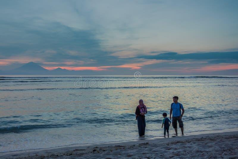 Moslimfamilie die langs het strand in de zonsondergang lopen royalty-vrije stock afbeeldingen