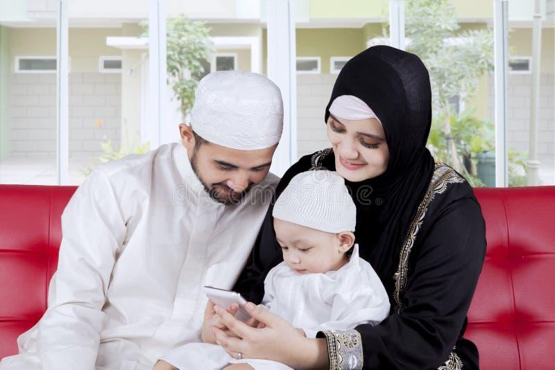 Moslimfamilie die slimme telefoon met behulp van stock fotografie