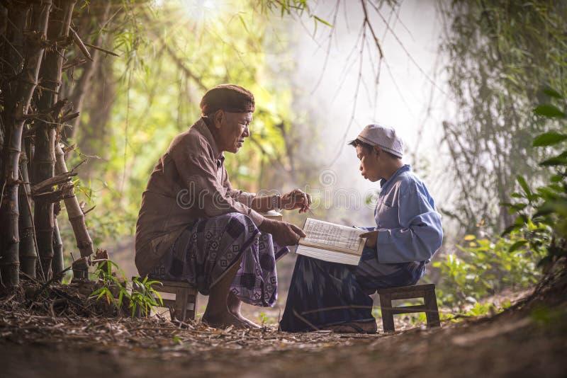 Moslimgrootvader leert neef om een boek te lezen Moslims lezen uit de kroon stock fotografie