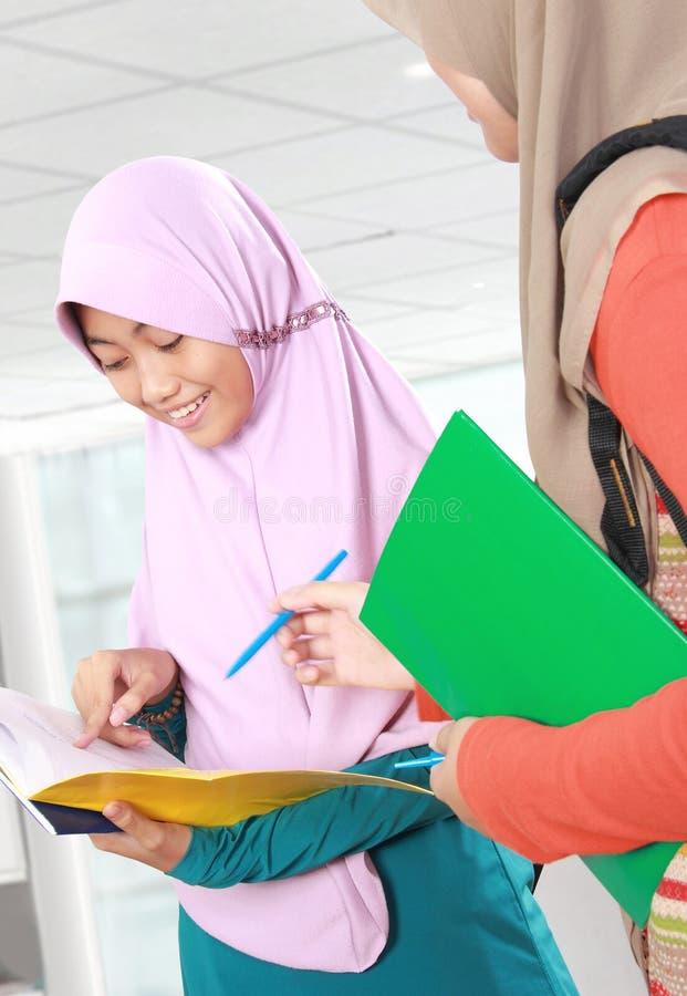 Moslimjong geitjestudent die iets in bibliotheek bespreken stock afbeeldingen