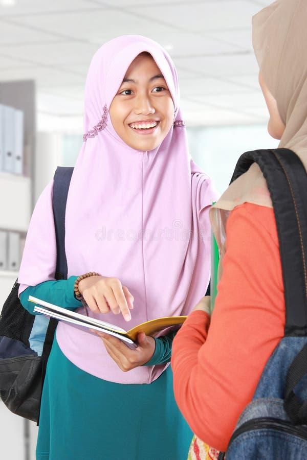 Moslimjong geitjestudent die iets in klaslokaal bespreken stock fotografie