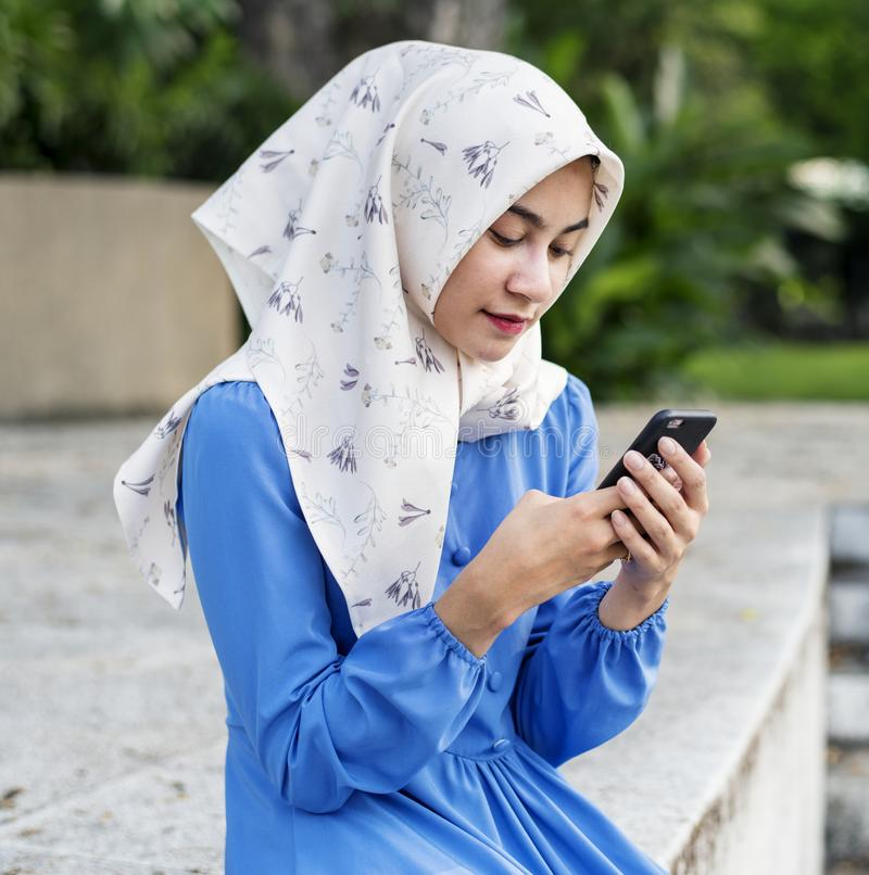 Moslimmeisje die een smartphone in het park gebruiken stock foto's