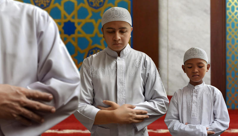 Moslimmens en het moslimjong geitje bidden stock foto