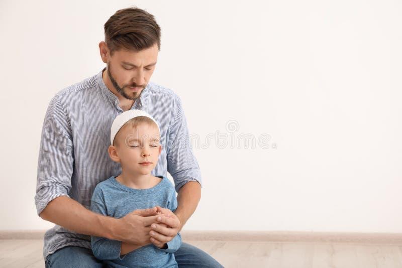 Moslimmens en zijn zoon die samen binnen bidden stock foto's