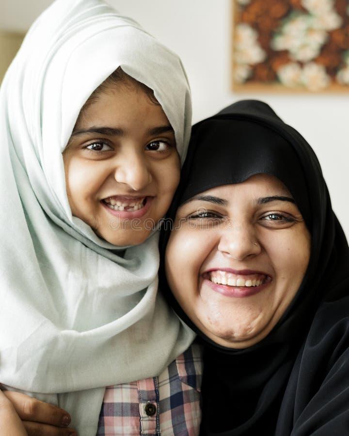 Moslimmoeder die haar dochter met liefde koesteren stock afbeeldingen