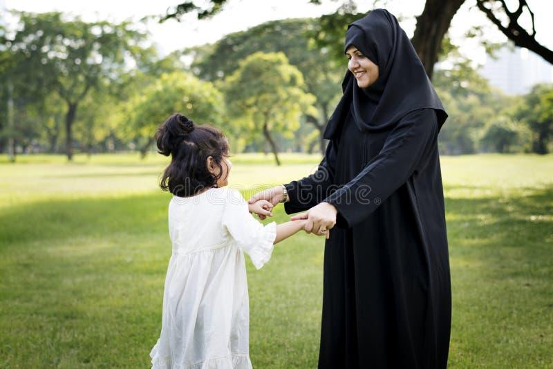 Moslimmoeder die haar dochter spelen bij park stock afbeelding