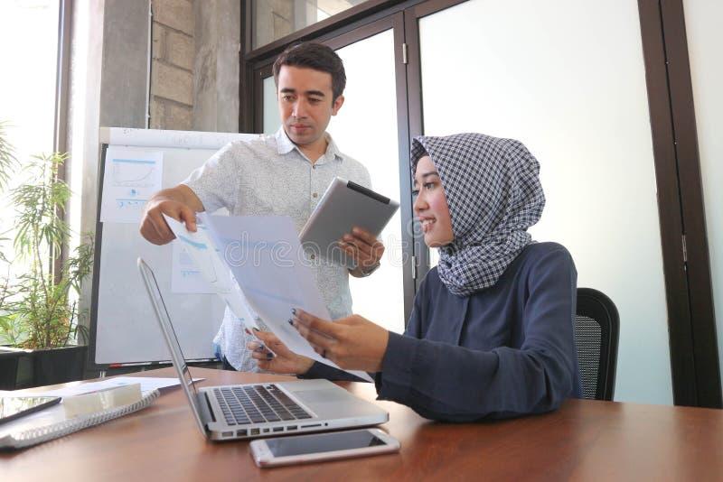 Moslimonderneemster en knappe mens die samen met laptop tablet en document dichtbij vensters met het witte raad grafisch tonen we royalty-vrije stock afbeelding