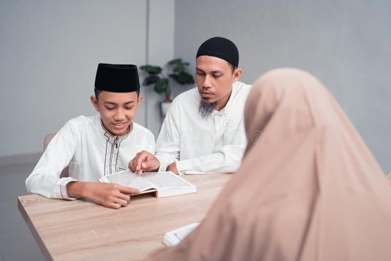Moslimvader die zijn zoon onderwijzen hoe te om quran te lezen stock foto