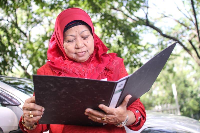 Moslimvrouw die een dossier houden stock foto