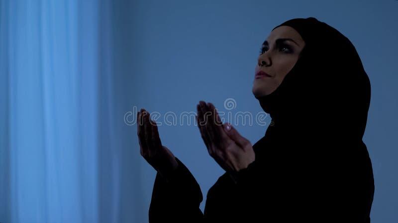 Moslimvrouw die met open handen bidden, die op hemel, god een beroep doen die, geloof zegenen stock foto