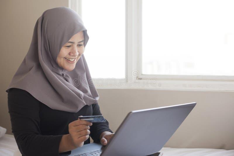 Moslimvrouw die Online Aankoop maken stock foto's