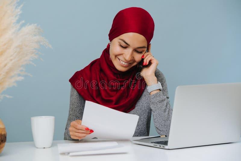 Moslimvrouw die op de telefoon spreken en aan een laptop zitting bij een lijst werken royalty-vrije stock fotografie