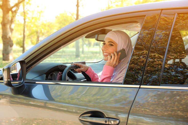 Moslimvrouw die op telefoon in bestuurderszitplaats spreken stock foto
