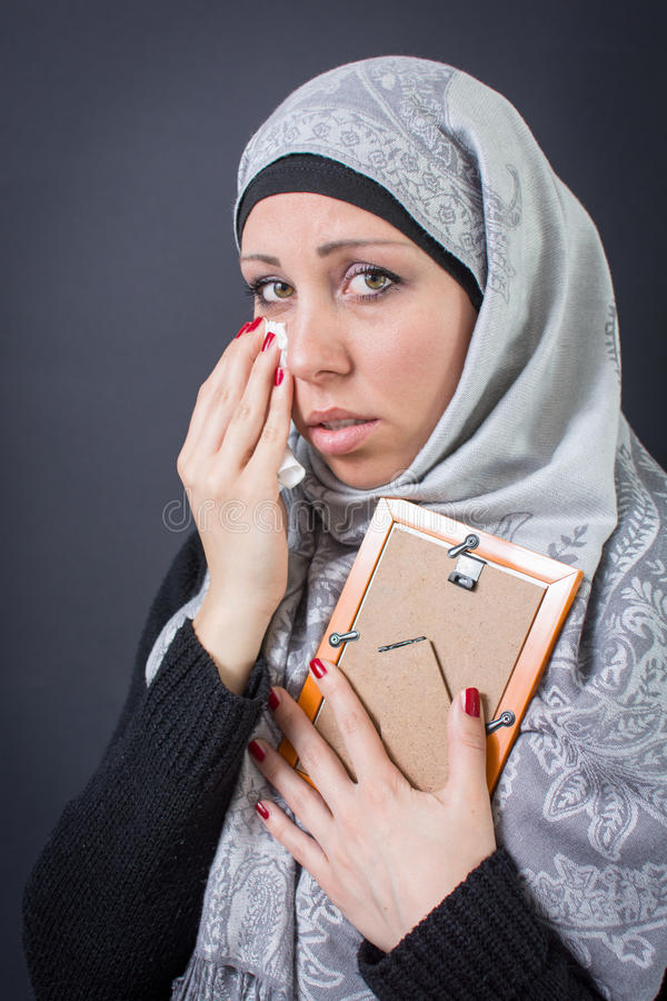 Moslimvrouw die over een foto jammeren royalty-vrije stock afbeelding