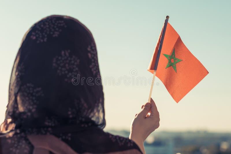 Moslimvrouw in sjaal met de vlag van Marokko van bij zonsondergang stock afbeelding