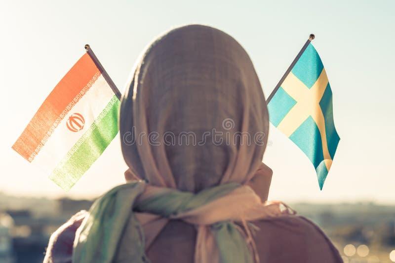 Moslimvrouw in sjaal met Zweedse en Iraanse vlaggen van bij zonsondergang Concept stock afbeeldingen